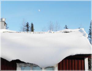 Hustak vid dålig isolerad vind. Snötäcket har tinat vid taknocken